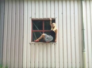 Gefährliche Pose in Fensterrahmen